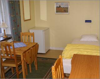 Enkelrum på vandrarhemmet med säng, bord, stolar med mera