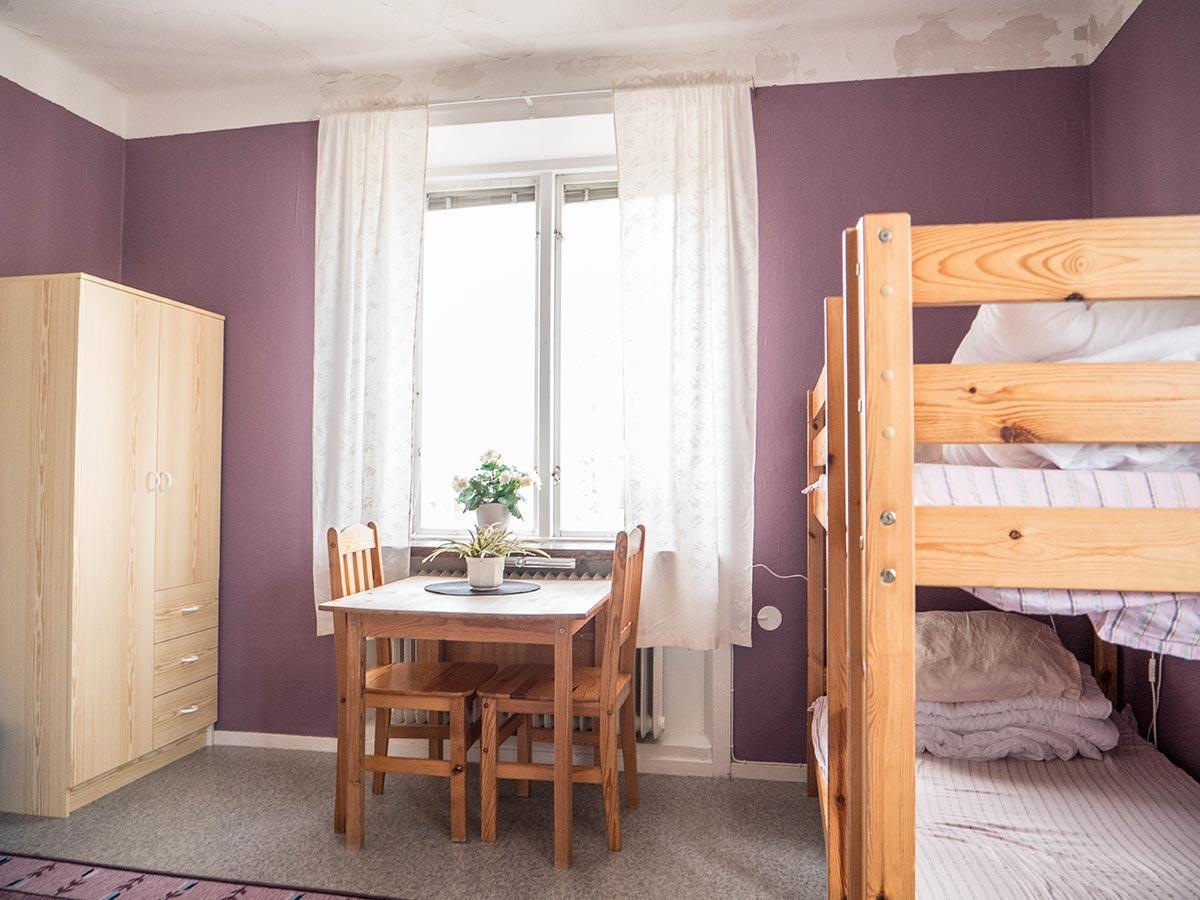 Flerbäddsrum på vandrarhemmet med 6-8 sovplatser. Våningssängar, bord och stolar
